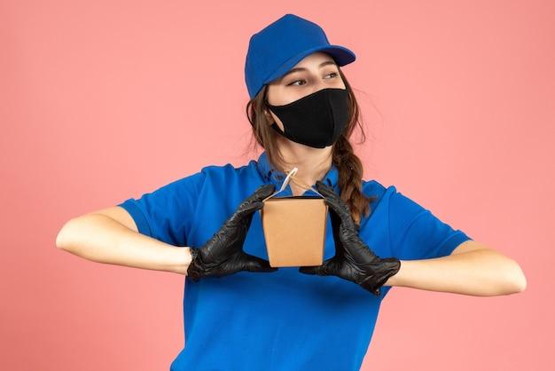 Colpo a metà corpo di una ragazza del corriere impegnata che indossa maschera medica e guanti che tengono una piccola scatola in posa per la fotocamera su sfondo color pesca pastello