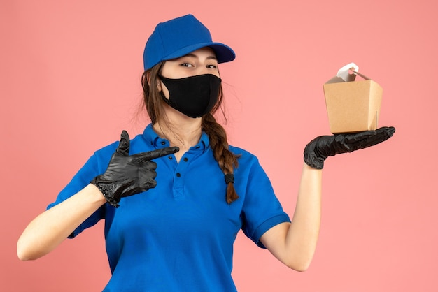 Colpo a metà corpo di una ragazza sicura del corriere che indossa maschera medica e guanti che tengono una piccola scatola in posa per la fotocamera su sfondo color pesca pastello