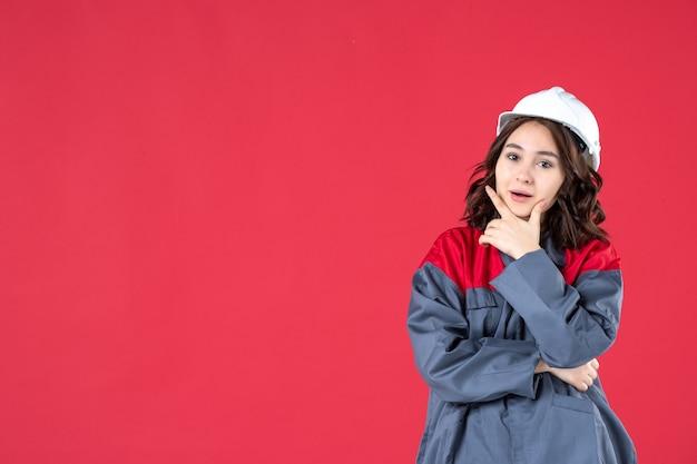 Colpo a metà corpo di un costruttore femminile fiducioso in uniforme con elmetto e concentrato su qualcosa su sfondo rosso isolato