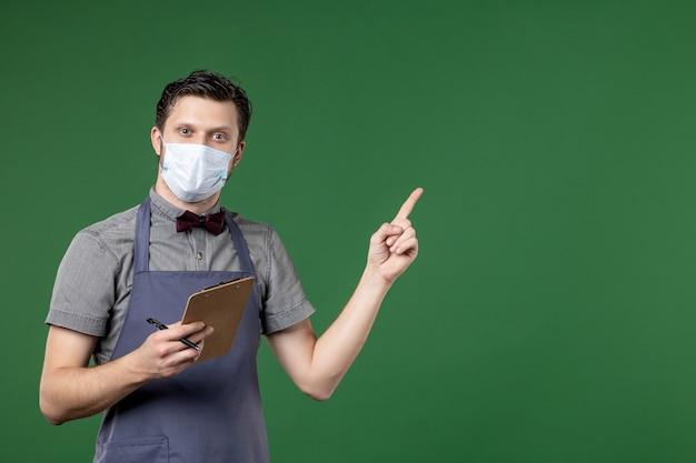 Colpo a metà corpo di un ragazzo fiducioso server in uniforme con maschera medica e tenendo la penna del libretto degli assegni rivolta verso l'alto sul lato sinistro su sfondo verde
