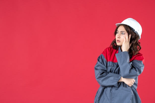 Colpo a metà corpo di un costruttore femminile confuso in uniforme con elmetto e che pensa profondamente su sfondo rosso isolato