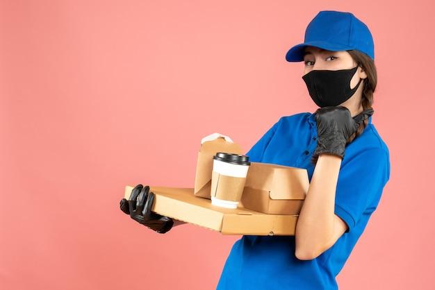 Colpo a metà corpo della ragazza del corriere che indossa maschera medica e guanti che tengono gli ordini che puntano indietro su sfondo color pesca pastello
