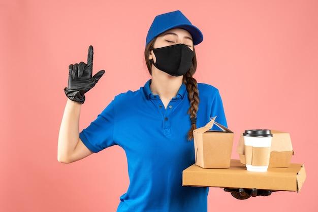 Colpo a metà corpo della ragazza del corriere che indossa maschera medica e guanti che tengono gli ordini rivolti verso l'alto su sfondo color pesca pastello