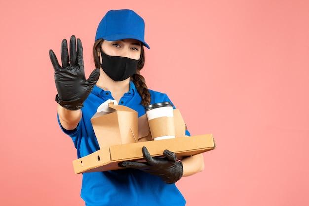 Colpo a metà corpo della ragazza del corriere che indossa maschera medica e guanti che tengono gli ordini che mostrano cinque su sfondo color pesca pastello