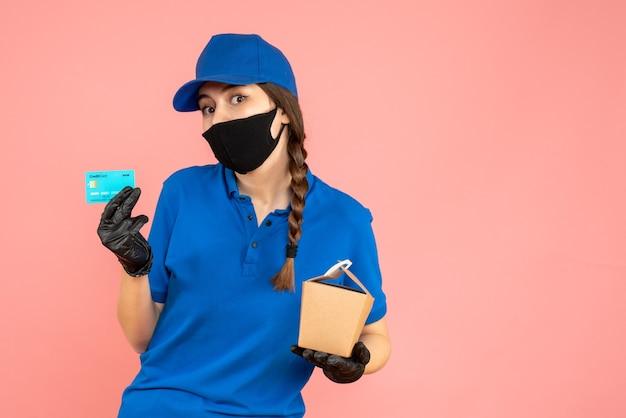 Colpo a metà corpo della ragazza del corriere che indossa maschera medica e guanti che tengono piccola scatola e carta di credito su sfondo color pesca pastello