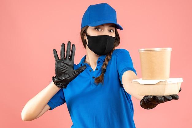 Colpo a metà corpo della ragazza del corriere che indossa maschera medica e guanti che tengono una piccola scatola di caffè che mostra cinque su sfondo di pesca pastello