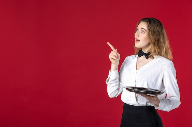Half body shot of curious waitress girl butterfly on the neck and holding tray pointing up on red background