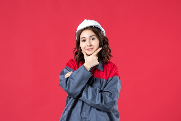 Colpo a metà corpo di una donna felice in uniforme con elmetto e concentrata su qualcosa su sfondo rosso isolato