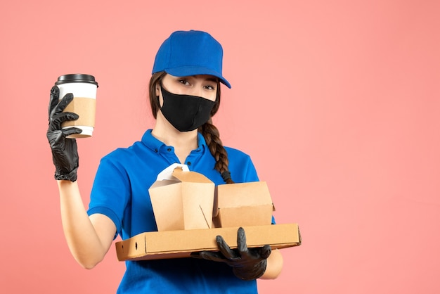 Colpo a metà corpo di una laboriosa corriere che indossa maschera medica e guanti che tengono ordini su sfondo color pesca pastello