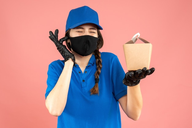 Colpo a metà corpo di una ragazza del corriere nervoso che indossa una maschera medica e guanti che tengono una piccola scatola su uno sfondo di pesca pastello