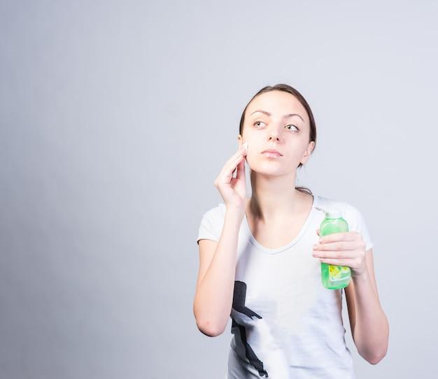 ボトルを持って左上を見ながら、洗顔料で綿を使って頬をこすり洗いする若い女性のハーフボディショット。ライトグレーの背景でスタジオでキャプチャされました。