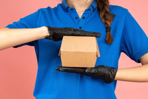 Снимок половины тела девушки-курьера в черных перчатках, держащей коробочку на пастельно-персиковом фоне