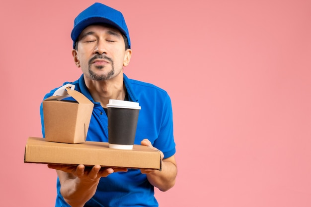 Половина тела мечтательного парня-доставщика в шляпе, держащего заказы