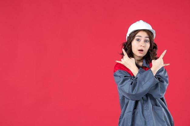 모자를 쓰고 격리된 빨간색 배경에서 양쪽을 가리키는 여성 건축업자의 반신
