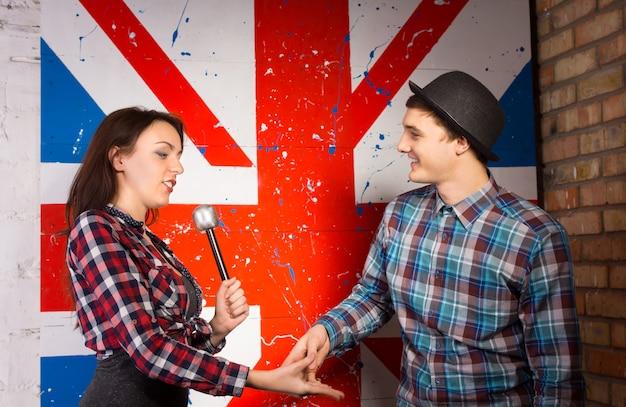 巨大な英国旗のプリントで、両方のカジュアルな服装で、インタビュイーの男性と握手しようとしているインタビュアーの女性のハーフボディショット。