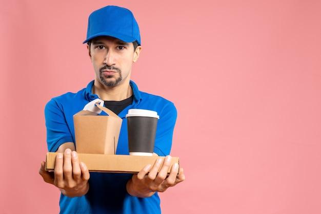 パステル調の桃の背景に注文する帽子をかぶった満足した男性配達員の半身ショット