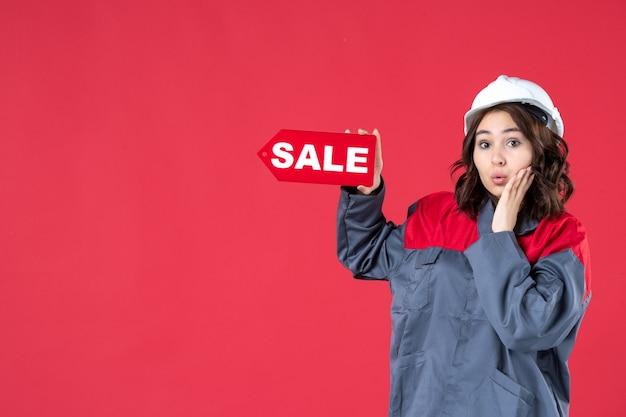 격리된 빨간색 배경에 단단한 모자를 쓰고 판매 아이콘을 가리키는 제복을 입은 놀란 여성 노동자의 반신 사진