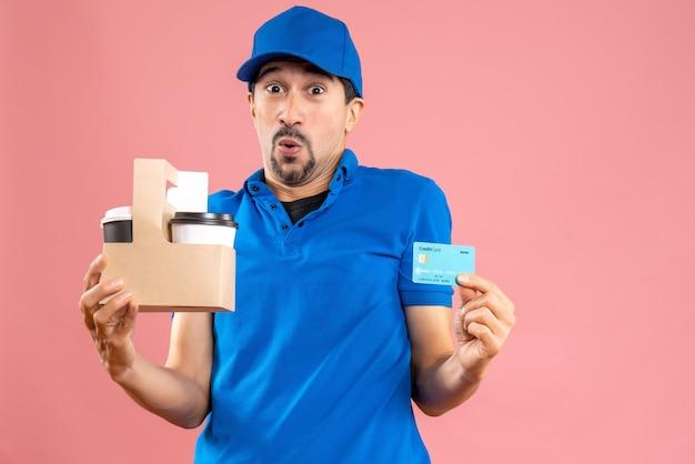 注文と銀行カードを保持している帽子をかぶった驚いた男性の配達員の半身ショット
