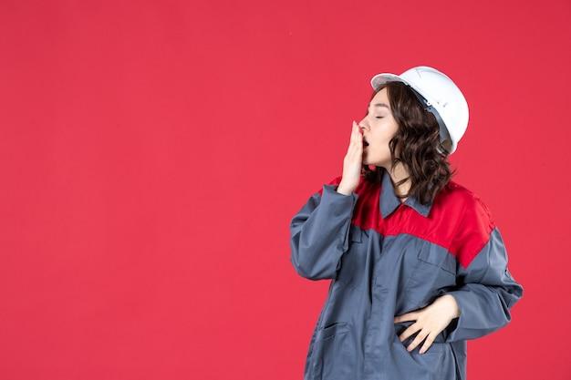 ヘルメットと孤立した赤い背景のあくびと制服を着た疲れた女性ビルダーの半身ショット