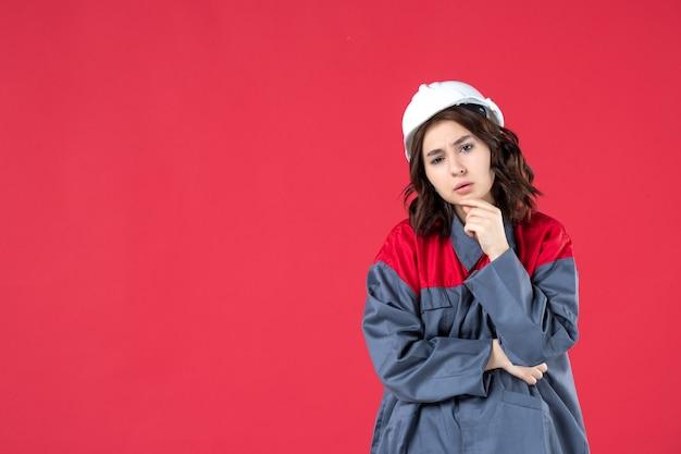 Снимок половины тела удивленной женщины-строителя в униформе с каской, сконцентрированной на чем-то на изолированном красном фоне