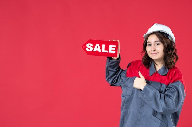 Colpo a metà corpo di una lavoratrice sorridente in uniforme che indossa elmetto e indica l'icona di vendita che fa un gesto ok su sfondo rosso isolato