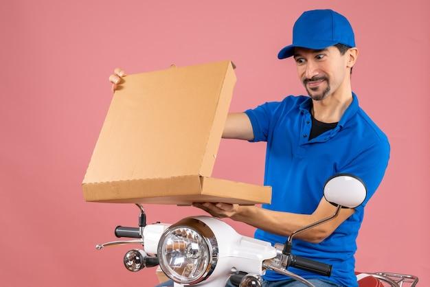 Colpo a metà corpo di un uomo sorridente che consegna il fattorino che indossa un cappello seduto sull'ordine di apertura dello scooter
