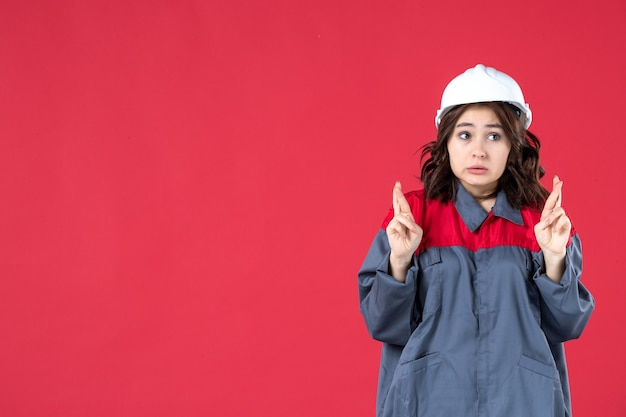 Half body shot of surprised female builder in uniform with hard hat and crossing her fingers on isolated red background