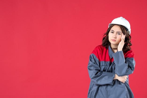 Colpo a metà corpo di un costruttore femminile sorpreso in uniforme con elmetto e che pensa profondamente su sfondo rosso isolato