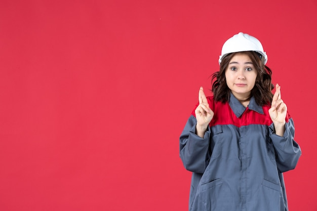 Half body shot of uncertain female builder in uniform with hard hat and crossing her fingers on isolated red background