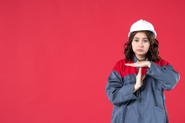 Half body shot of unhappy female builder in uniform with hard hat making stop gesture on isolated red background