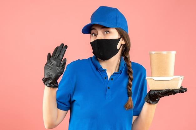Colpo a metà corpo di una ragazza del corriere preoccupata che indossa maschera medica e guanti che tengono una piccola scatola di caffè su sfondo di pesca pastello peach