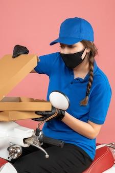 Colpo a metà corpo di una giovane curiosa corriera che indossa maschera medica e guanti seduti su uno scooter che apre scatole su sfondo color pesca pastello