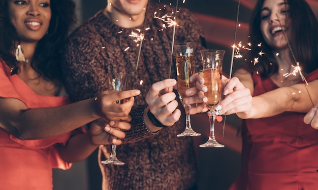 Half burned out. multiracial friends celebrate new year and holding bengal lights and glasses with drink