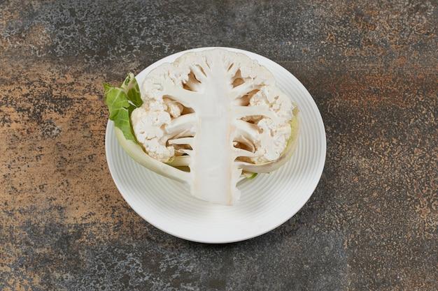 Mezzo cavolfiore nel piatto, sulla superficie del marmo