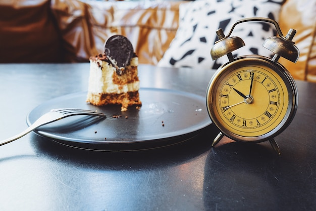 黒いテーブルの上の半分のチョコレートケーキと目覚まし時計。