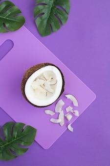 紫の背景のキッチンボード上の半分のココナッツとチップ