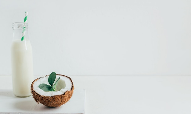 Half coconut and bottle with coconut milk on white background