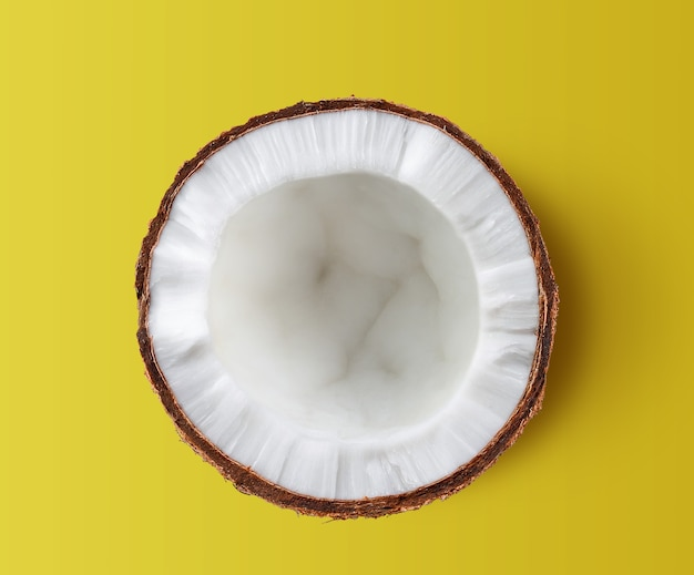 Half coconut isolated on yellow background