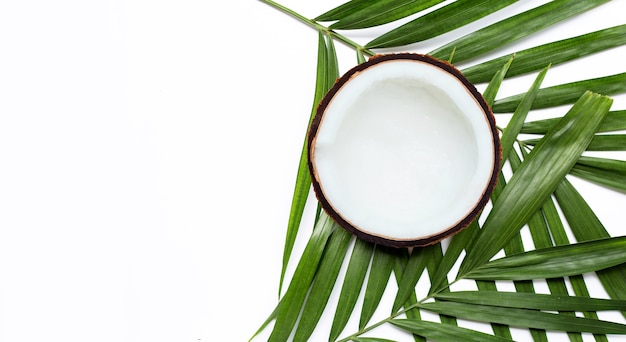 Половина кокоса на тропических пальмовых листьях. вид сверху