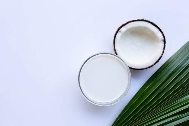 Half coconut with glass bowl of coconut milk on white background.
