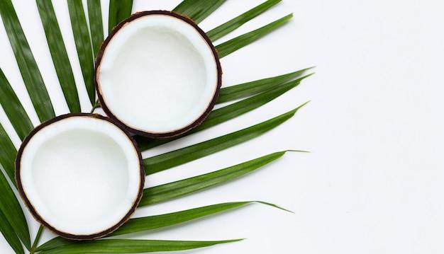 Половина кокосов на тропических пальмовых листьях. вид сверху