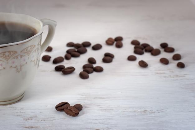 白のスチームとコーヒー豆とコーヒーの半分のカップ