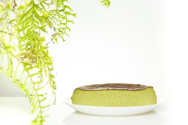 白い背景に分離された抹茶緑茶バスク焦げたチーズケーキの半分のカップ。