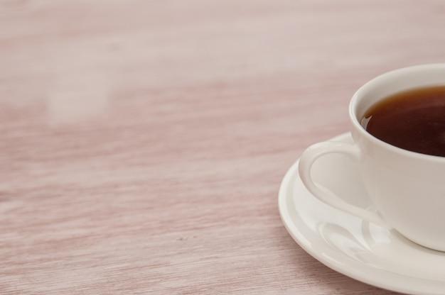 Половина чашки чая на светлом старом деревянном столе