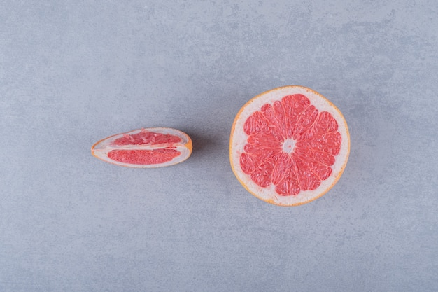 Половина и ломтик грейпфрута на серой поверхности