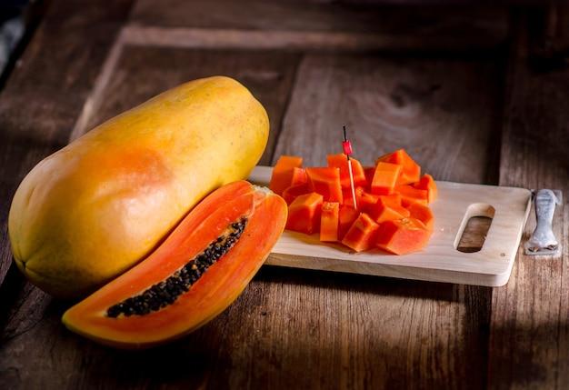 Полурезанные и целые папайи плоды на деревянном столе