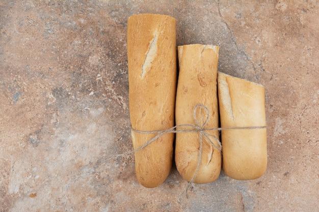 Pane baguette tagliato a metà su fondo di marmo