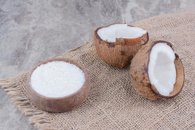 Noci di cocco tagliate a metà e ciotola di zucchero su fondo di pietra.