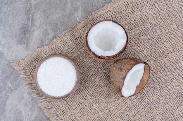 Noci di cocco tagliate a metà e ciotola di zucchero sulla superficie della pietra.