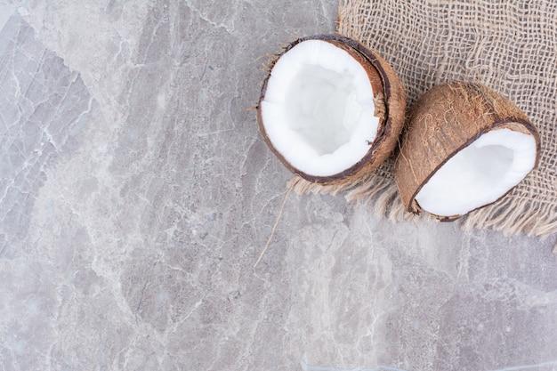 Noci di cocco tagliate a metà sulla superficie di pietra con tela.